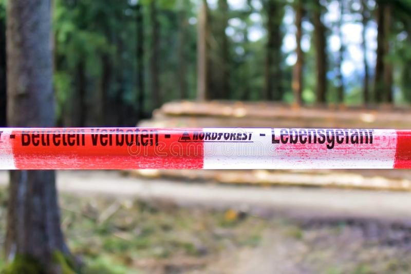 Red and white striped warning barrier tape in forest saying `Do not enter` and `Danger to life` in German royalty free stock images