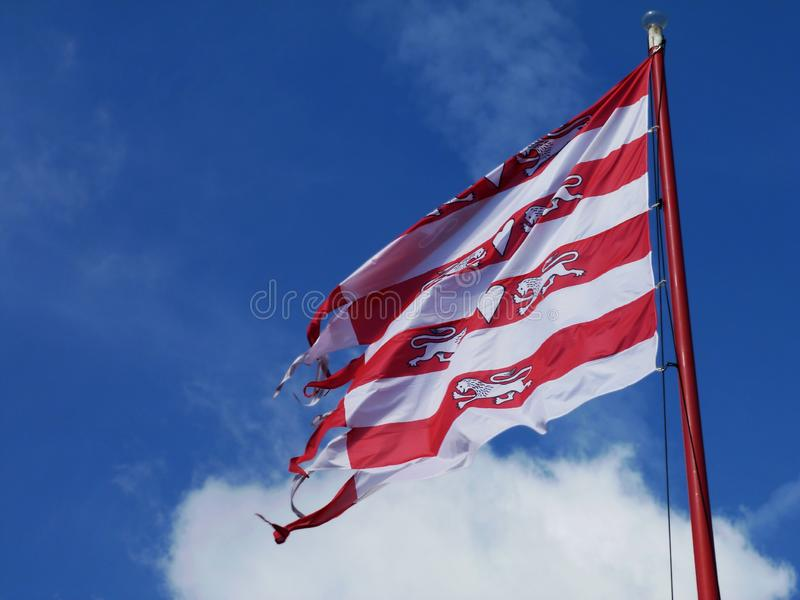 Red and white striped waving flags in strong wind under blue sky stock photo