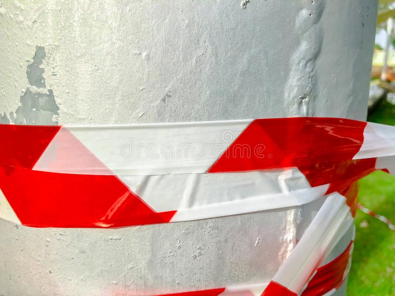 Red white tape to prohibit twisting the stab in the street. Close up shot. Red white tape to prohibit twisting the stab in the street stock photography