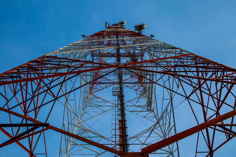 Red white telecommunication tower against blue sky - bottom view. Telecommunication tower mast TV antennas wireless technology with blue sky royalty free stock photography