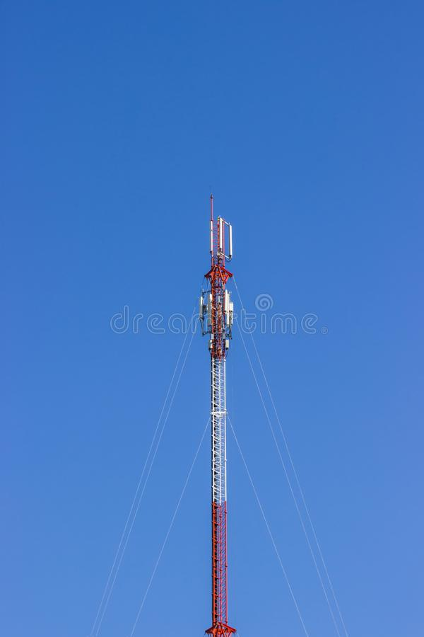 Red and white Telecommunication tower in a day of clear blue sky stock photo