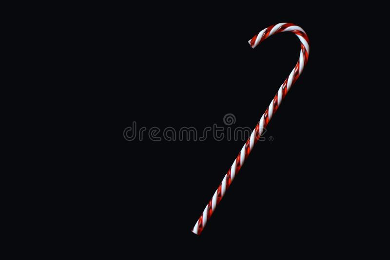 Red and white traditional Christmas candy cane on black background greeting card motive royalty free stock photos