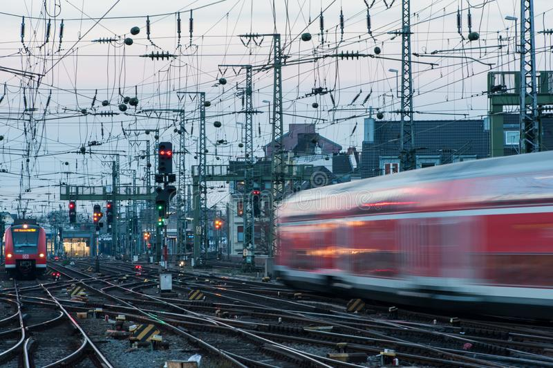 Red and white train in motion in Europe. On rails and many pillars and electricity cables near main station stock photography