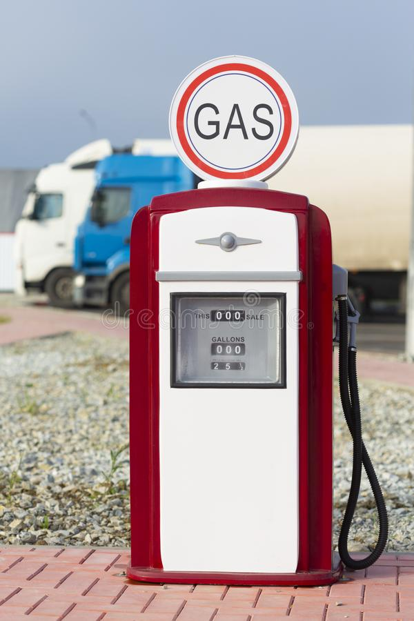 Red and white vintage gasoline fuel pump. With cargo trucks in the background royalty free stock photos