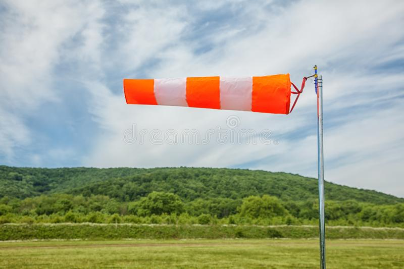 Red and white wind sock on blue sky, mounting and clouds background. Close-up stock images