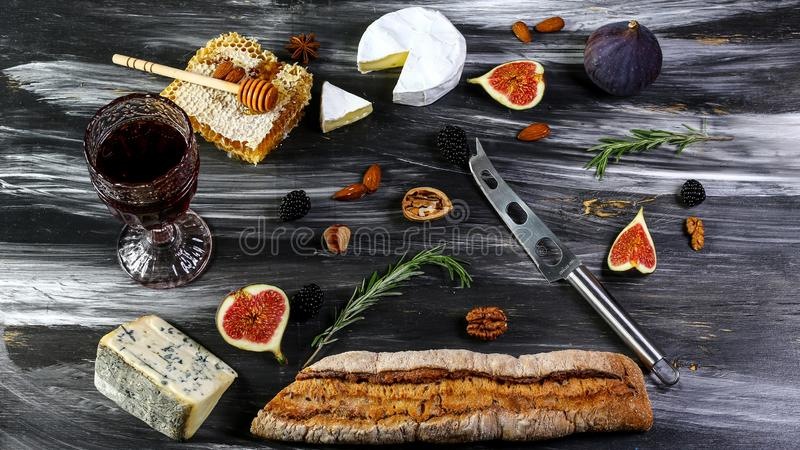 Red and white wine plus different kinds of cheeses cheeseboard on rustic wooden table. French food tasting party or feast scenery royalty free stock images