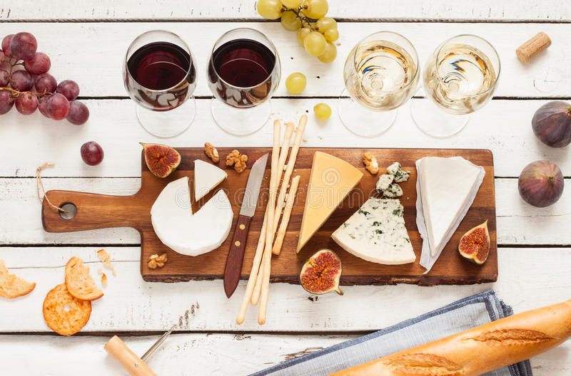 Red and white wine plus different kinds of cheeses (cheeseboard). On rustic wooden table. French food tasting party or feast scenery from above (top view stock image