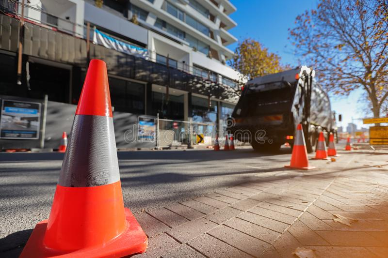 Red and white witches hat cone traffic warning sign. Red and white witches hat cone traffic sign barrier applying on busy street downtown on pedestrian footpath royalty free stock photo