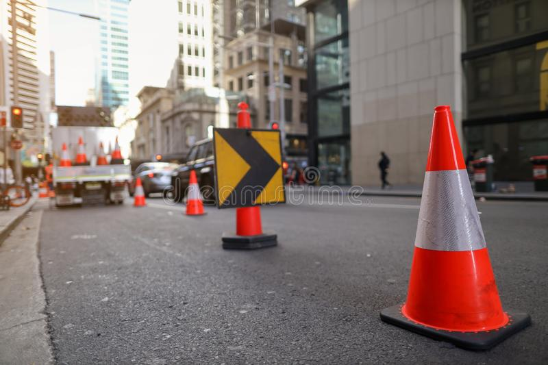 Red and white witches hat cone traffic warning sign barrier applying on busy street downtown on pedestrian footpath stock photography