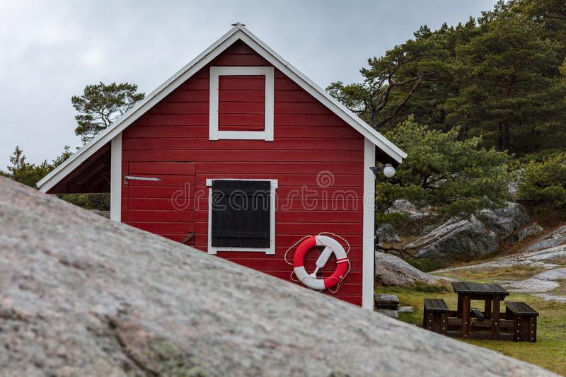 Red white wooden house on cliffs near sea royalty free stock photo