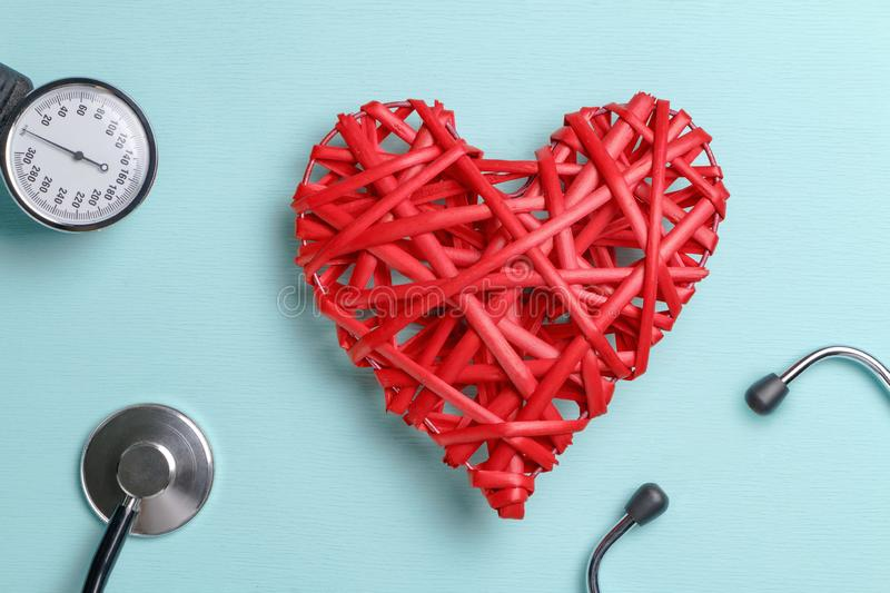 Red wicker heart on a blue table, next to a blood pressure cuff and stethoscope.  stock photography