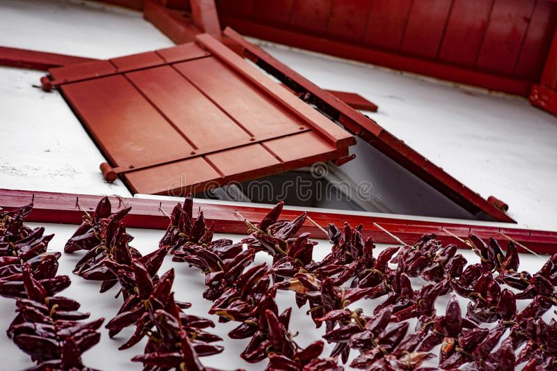Red window and chili - Espelette. Espelette is known for its dried red peppers, used whole or ground to a hot powder, used in the production of Bayonne ham. The royalty free stock photography