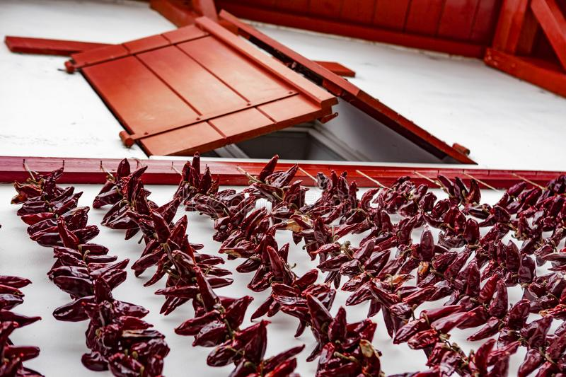 Red window and chili - Espelette. Espelette is known for its dried red peppers, used whole or ground to a hot powder, used in the production of Bayonne ham. The royalty free stock images