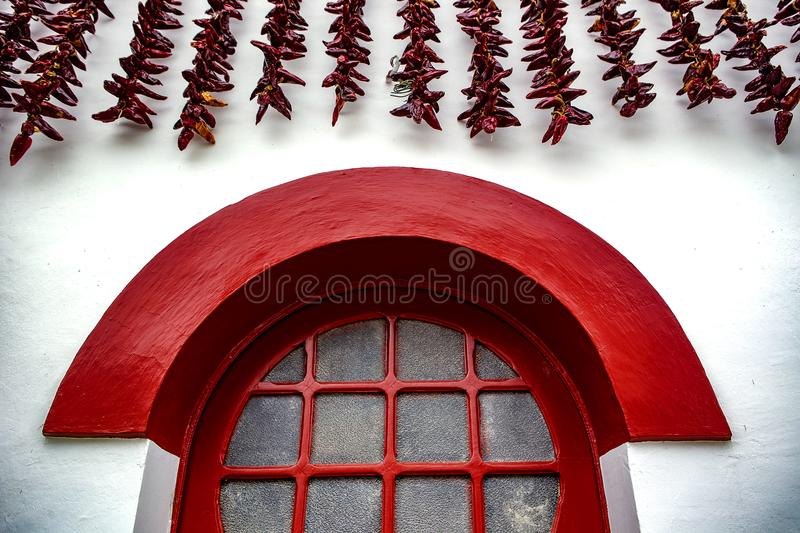 Red window and chili - Espelette. Espelette is known for its dried red peppers, used whole or ground to a hot powder, used in the production of Bayonne ham. The stock images