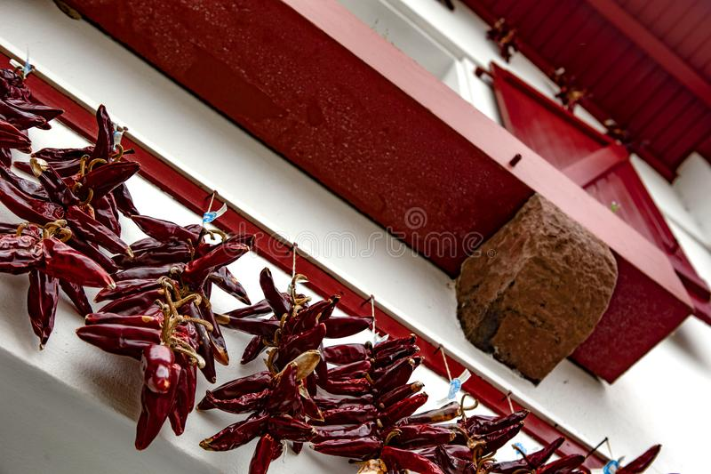 Red window and chili - Espelette. Espelette is known for its dried red peppers, used whole or ground to a hot powder, used in the production of Bayonne ham. The royalty free stock image