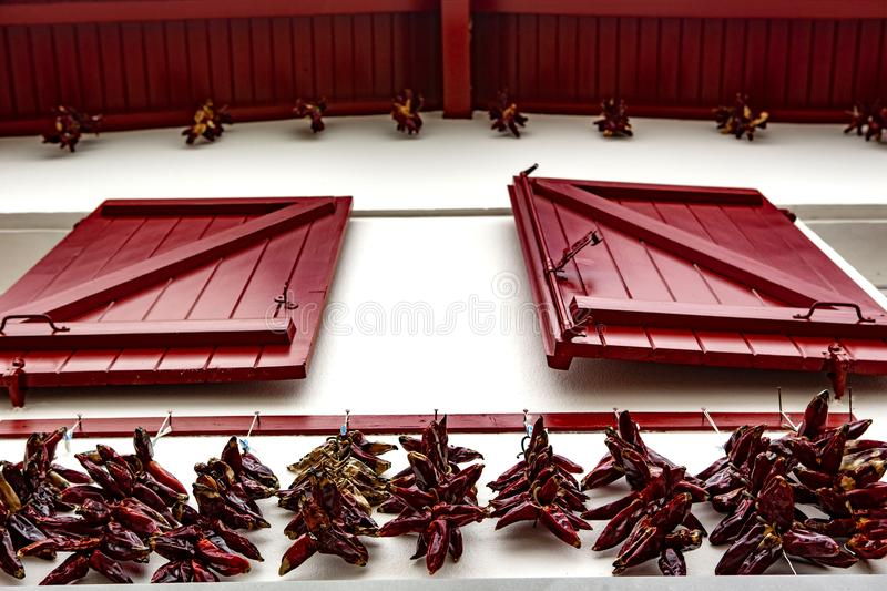 Red window and red chili - Espelette. Espelette is known for its dried red peppers, used whole or ground to a hot powder, used in the production of Bayonne ham stock images