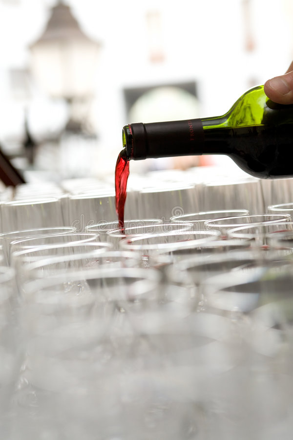 Red wine. Red French wine pour from a bottle in the glasses which are standing in a row stock photography