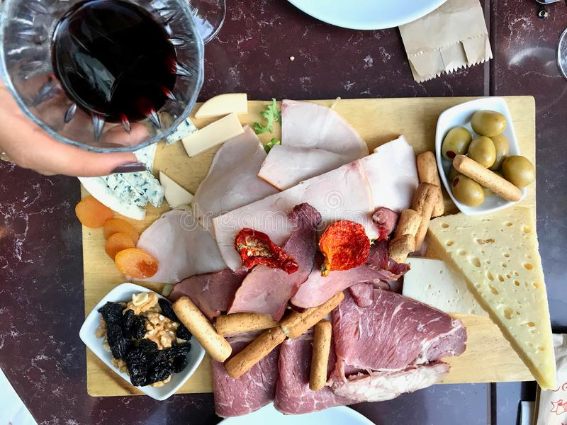 Red Wine And Assorted Cheese Plate, Smoked Beef, Ham, Salami, Green Olives with fruit stock photography