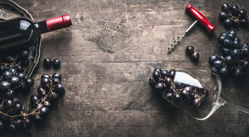 Red wine background with bottle and corkscrew , grapes and wine glass on dark vintage wooden stock images