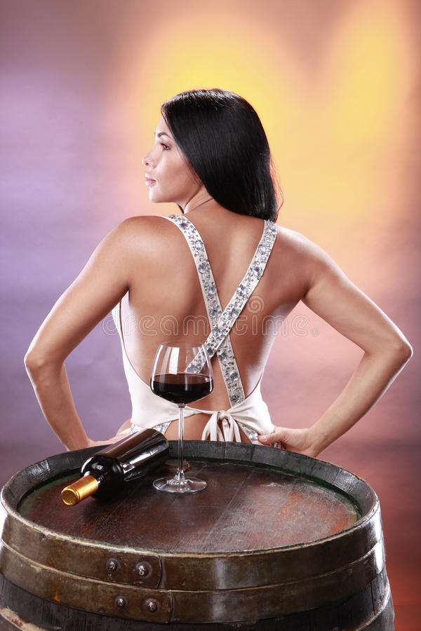 Red wine on a barrel. Cute brunette tasting red wine on a cellar's barrel stock images