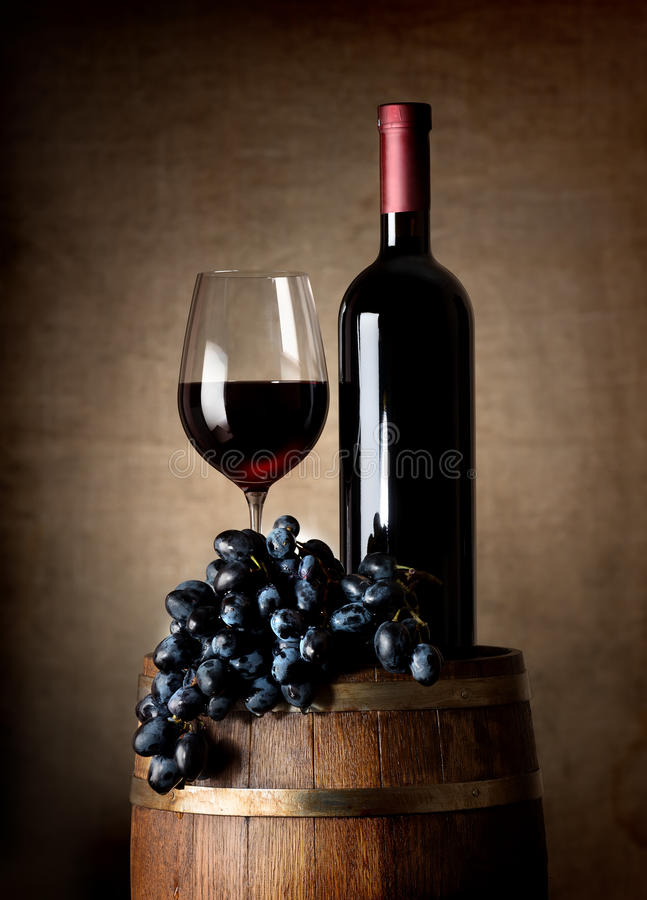Red wine with barrel and grapes. Bottle of red wine, wine glass, grapes and wooden barrel stock photos