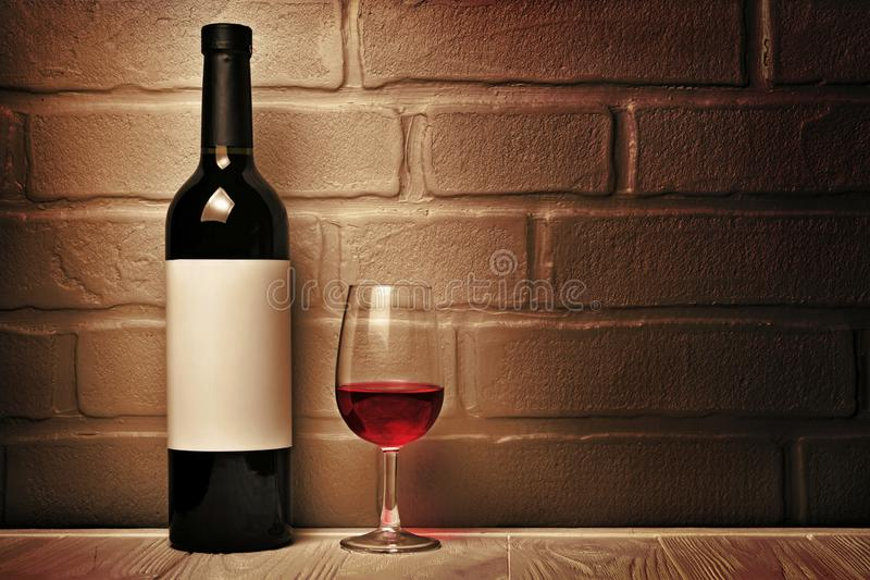 Red wine bottle with empty label and glass for tasting in cellar. On brown brick wall background royalty free stock images