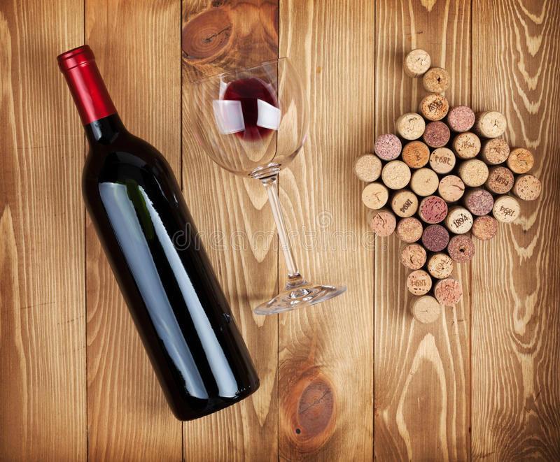 Red wine bottle, glass and grape shaped corks royalty free stock photo