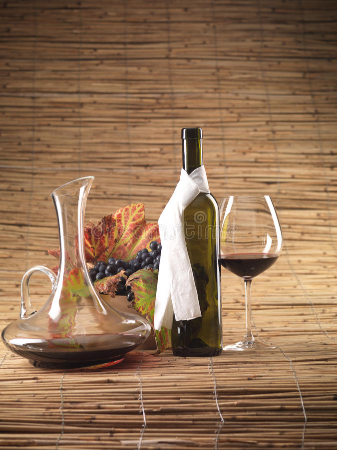 Red wine bottle, glass, grapes, decanter rustic