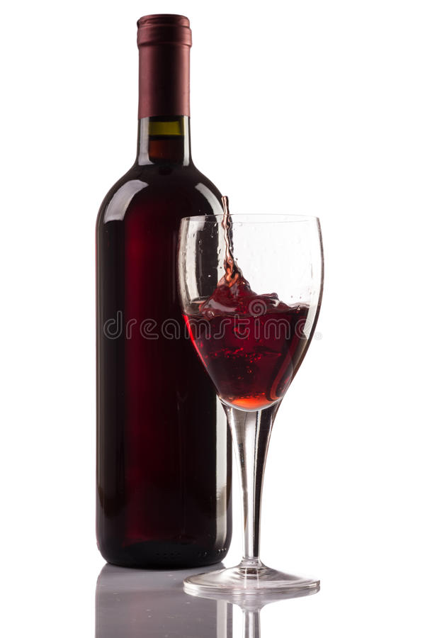 Red wine bottle and glass with splash on white background stock photo