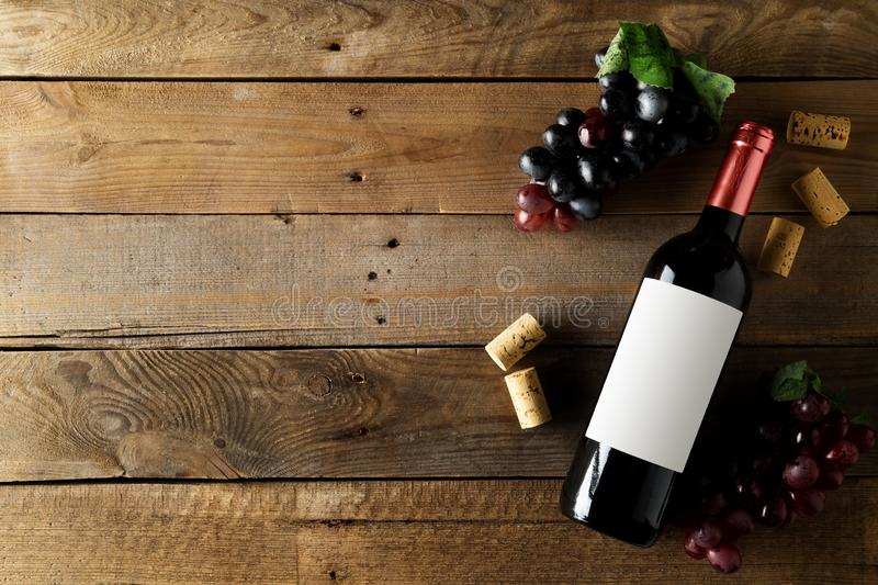 Red wine bottle with grapes and corks on brown rustic wooden table flat lay from above royalty free stock photography