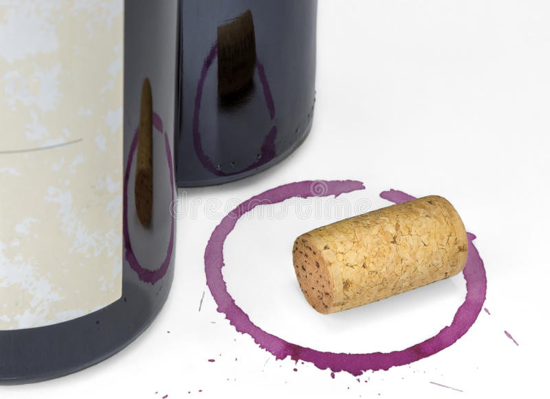 Red Wine Bottle, Cork, Glass Stain. Two red wines bottles, one with a blank label, and a cork on a wine glass stain with spatter, off white background stock photography