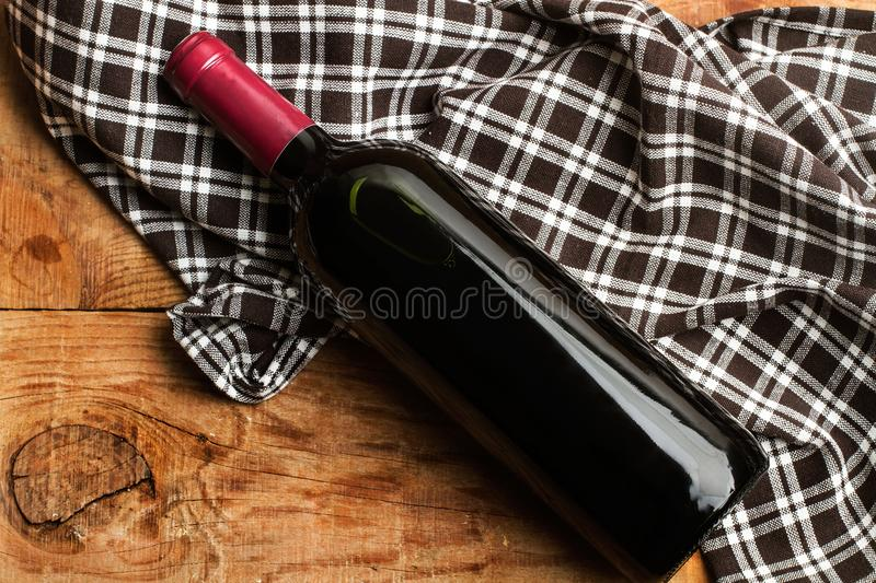 Red wine bottle on a serviette. Red wine bottle on a grid serviette stock photos
