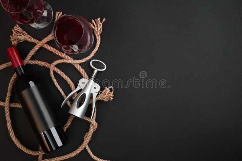 Red wine bottle, two glasses and corkscrew on black background. Top view with copy space stock photography
