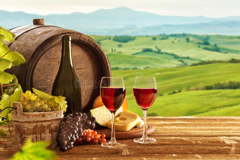 Red wine bottle and wine glasses with wodden barrel stock image