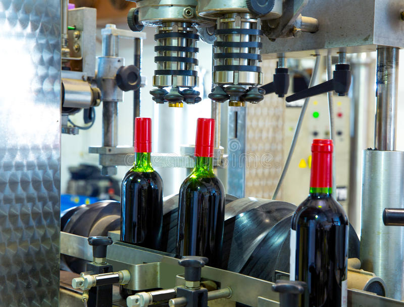 Red wine in bottling machine at winery royalty free stock image