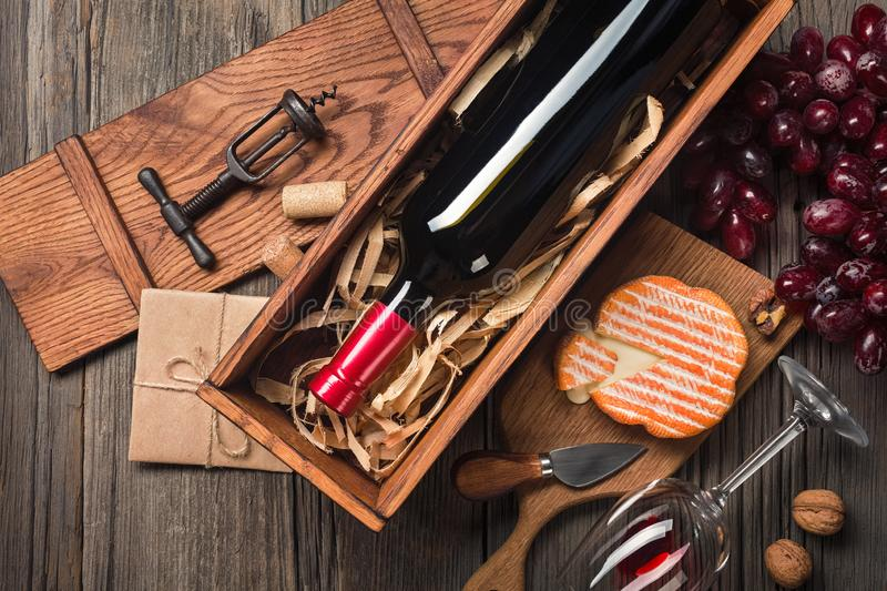 Red wine in a box with a glass, corkscrew and cream cheese on a wooden old table. Top view with space for your greetings royalty free stock images