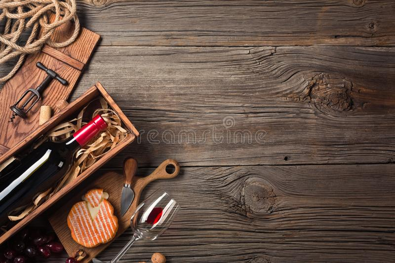 Red wine in a box with a glass, corkscrew and cream cheese on a wooden old table. Top view with space for your greetings royalty free stock photography