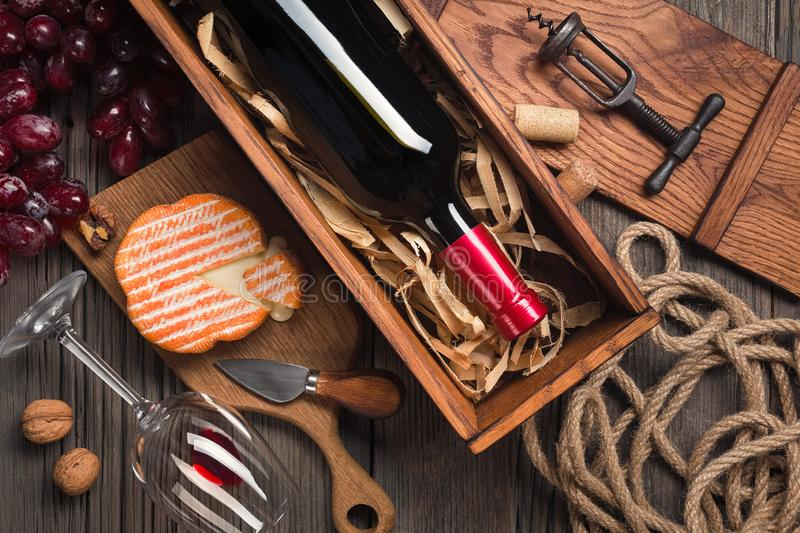 Red wine in a box with a glass, corkscrew and cream cheese on a wooden old table. Top view with space for your greetings royalty free stock photos