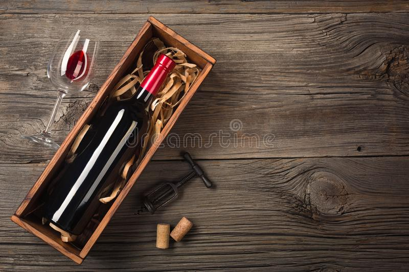 Red wine in a box with a glass and a corkscrew on a wooden table. Top view with space for your greetings royalty free stock image