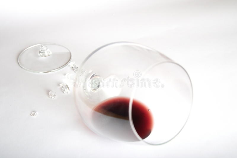 Red wine in broken glass. On white royalty free stock images