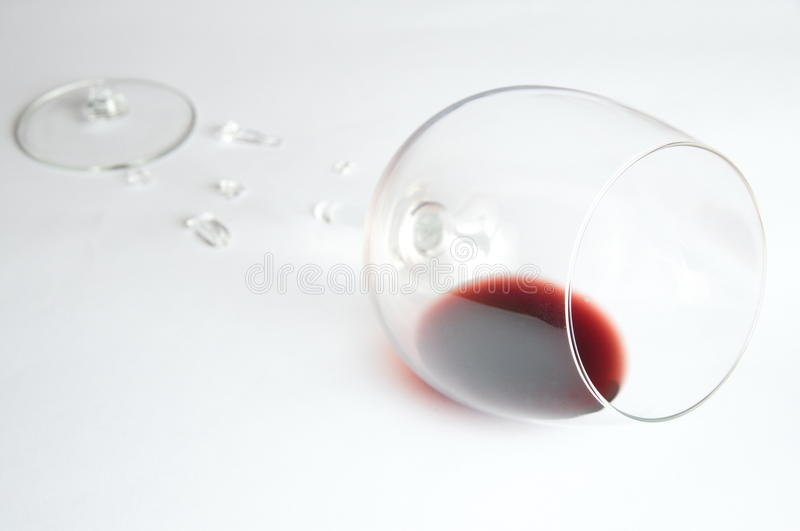 Red wine in broken glass. On white royalty free stock photo