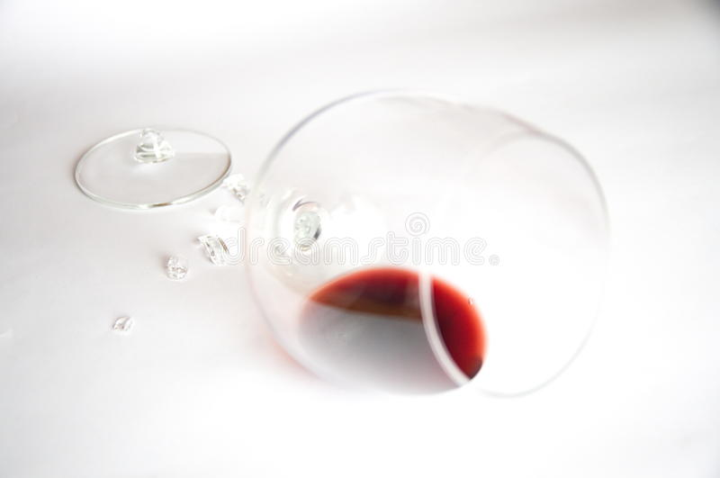 Red wine in broken glass. On white stock images