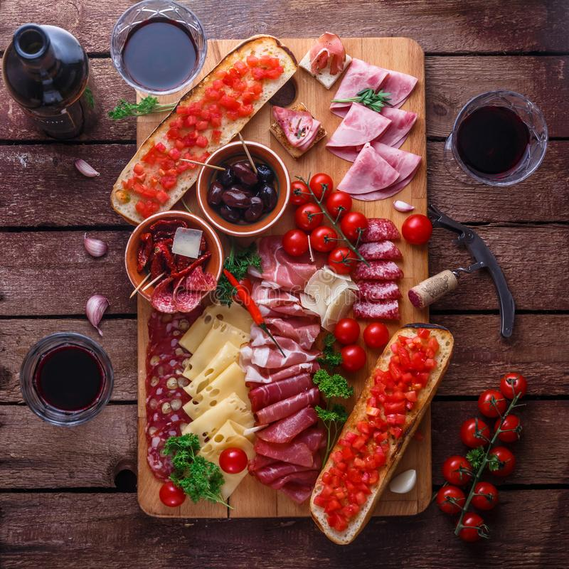 Red wine with charcuterie assortment on dark rustic table, flat lay stock photo