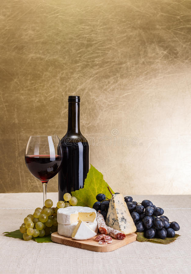 Red wine with cheese and blue grape snack stock image