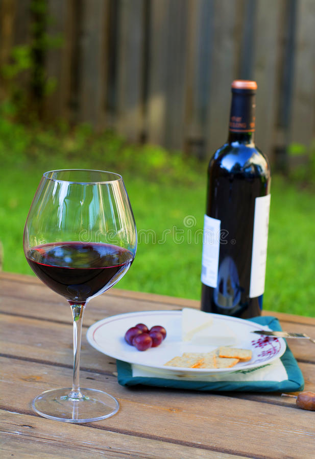 Red wine and cheese. Wine and cheese plus grapes. A Merlot and bottle of wine to enjoy on a patio. Summertime drinks. A glass of wine on the deck stock photography