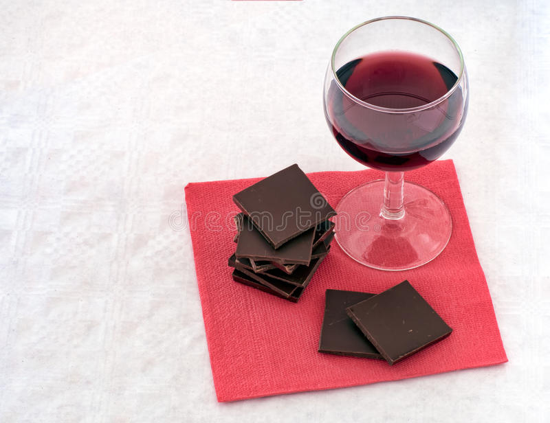 Red wine and chocolate on napkin,serviette. Healthy heart food. Red wine and plain chocolate snack on serviette stock image