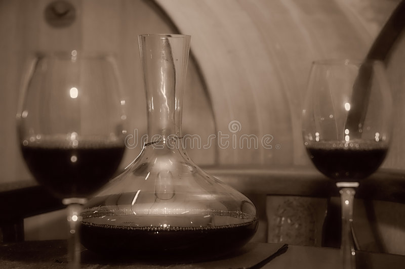 Red wine composition. A composition of a bottle of red wine and glass with wine cellar in background. Sepia toned stock images