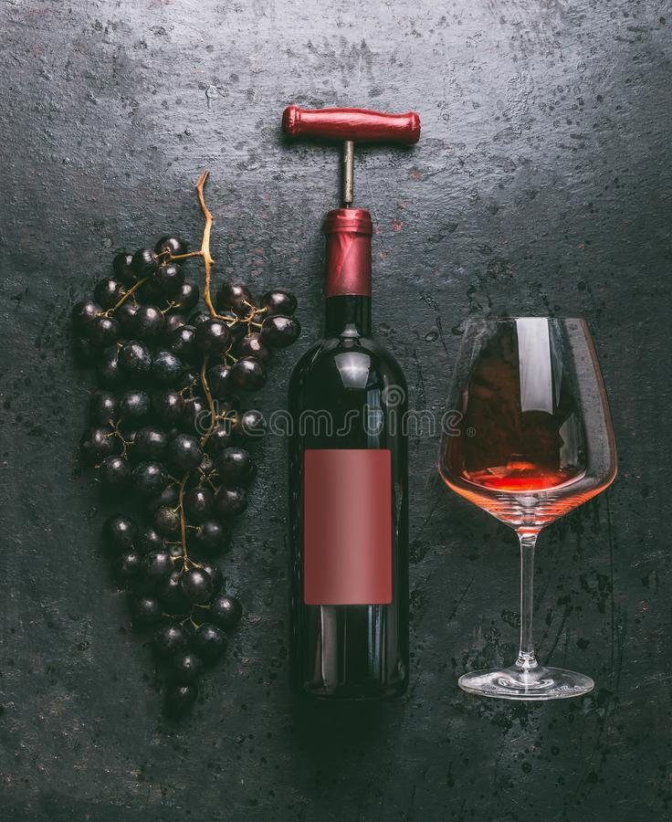 Red wine concept with bottle and vintage corkscrew, glass and grapes on retro black background, top view royalty free stock photos