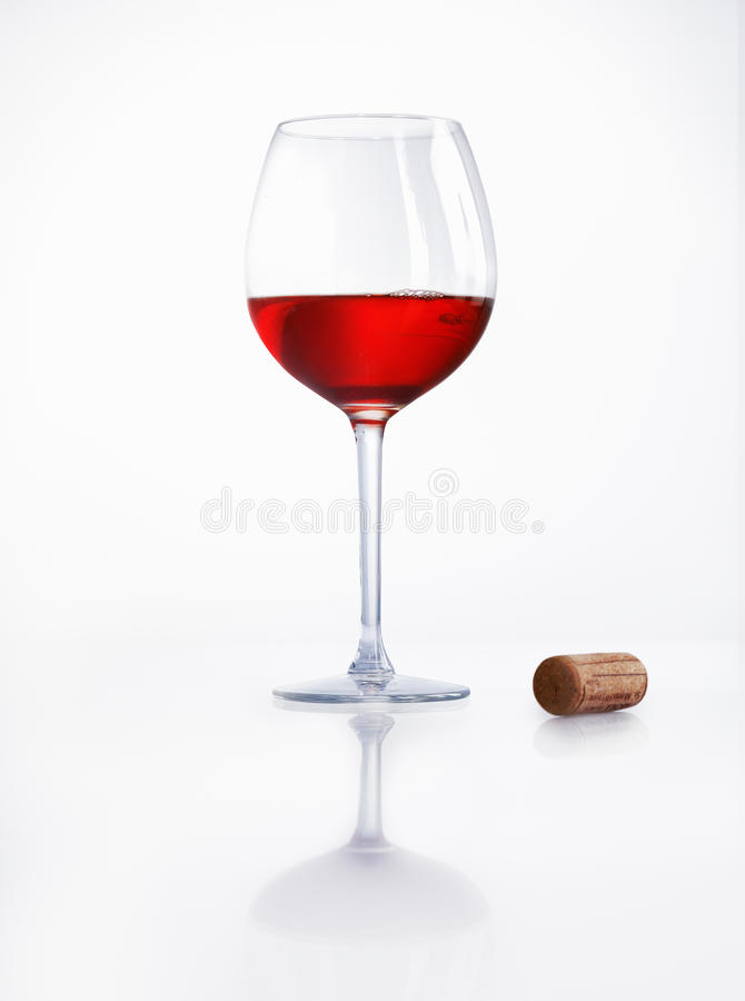 Red Wine And Cork. Glass half filled with red wine on a reflective white surface with a cork alongside at a party or celebration stock images