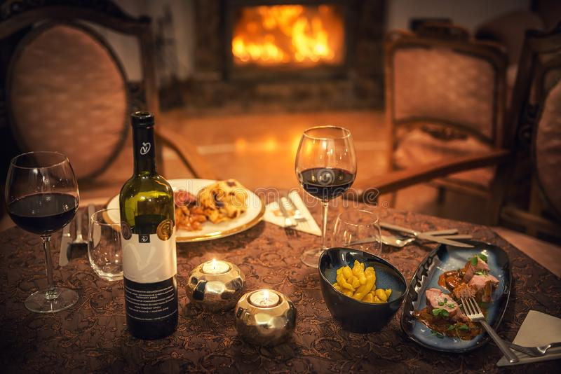 Red wine and food in restaurant, winter time, romantic dinner.  royalty free stock images